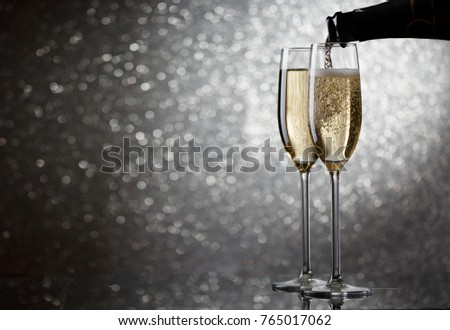 Picture of bottle with flowing champagne in wine glasses on gray background #765017062