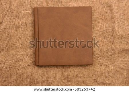 Picture of brown leather photo album cover on jute background. Keeping memories alive throughout the years