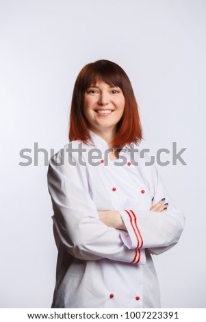 Picture of brunette chef in white robe with arms crossed at waist
