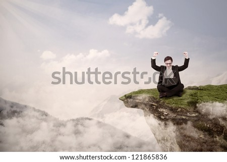 Picture of businessman with arms raised while sitting with his laptop on a mountain high