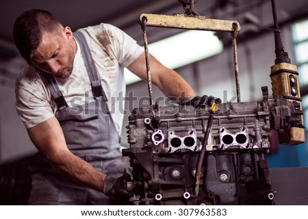 Picture of car engine hanging on hoist in repair shop
