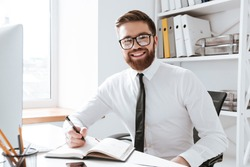 Picture of cheerful businessman sitting in office while writing notes. Looking at camera.