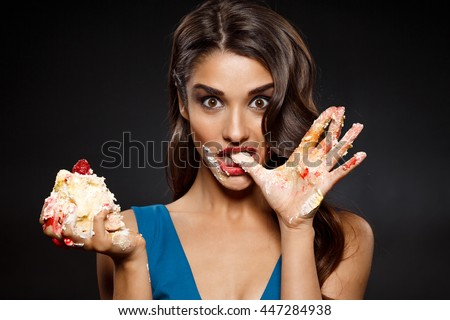 Picture of cheerful girl in blue dress eating  piece of cake