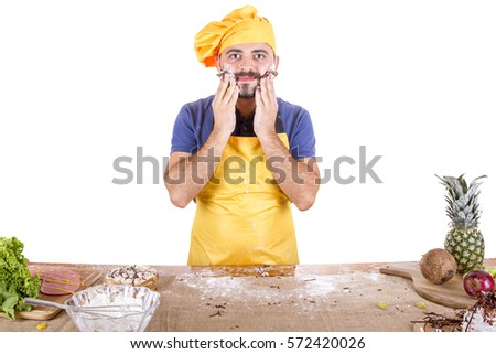 Picture of cheerful male chef in yellow uniform eating whole cake isolated on white background