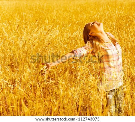 Picture of cheerful teenager having fun in countryside, cute happy female standing on wheat field with raised open hands and looking up, blond girl enjoying autumn nature, fall season #112743073