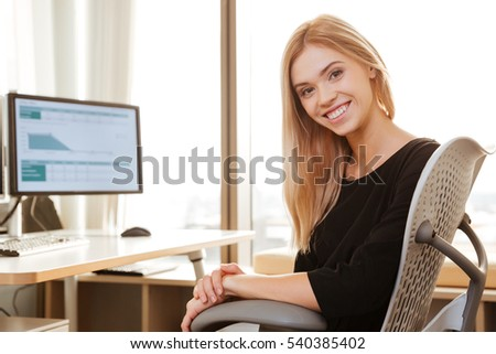 Picture of cheerful young woman worker sitting in office near computer. Look at camera.