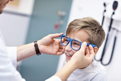 Picture of child optometry male optometrist optician doctor examines eyesight of little boy