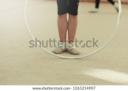 Picture of child's legs and a hoop in a sport gym club shooted during exercising on the background on passing child. Exercises with a hoop for gymnast