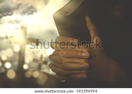 Picture of christian person praying to the GOD while holding a bible with crucifix symbol on the background