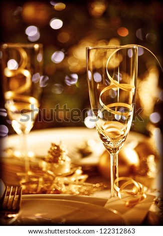 Picture of Christmas table setting, retro style photo, glasses for champagne, golden Christmastime decorations, white festive dishware, soft focus, New Year dinner, xmas eve, luxury home interior