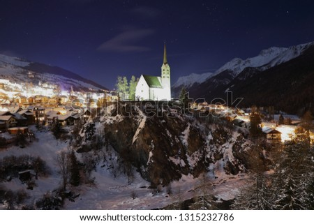 picture of church with tower in Scuol, Engadina, Switzerland at night with bright shining village and dark mountainscape in background. church shines in green light with river in front. in winter