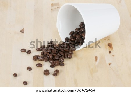 Picture of coffee beans and a white cup on a table