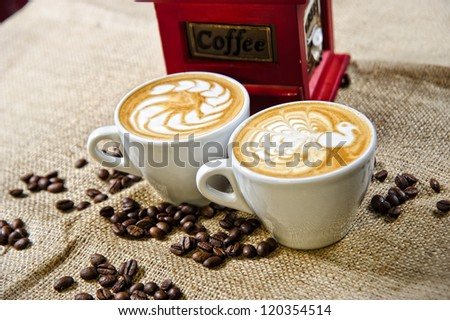Picture of coffee cups in front of manual coffee grinder.
