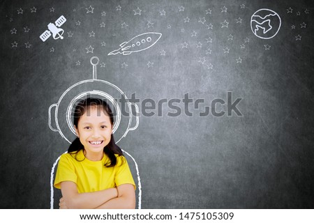 Picture of confident schoolgirl smiling at the camera while imagining being an astronaut #1475105309