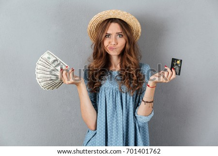 Picture of confused young woman standing over grey wall wearing hat holding money and credit card.
