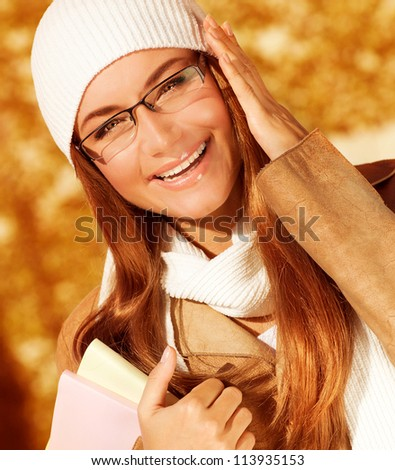 Picture of cute cheerful student girl in university autumn park, portrait of happy smiling teenager wearing stylish glasses, pretty smart pupil, back to school, education and knowledge concept
