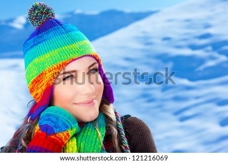 Picture of cute girl wearing colorful knitted hat with scarf and gloves on winter background, pretty teenager having fun on mountains covered snow, wintertime fashionable clothes, Christmas time