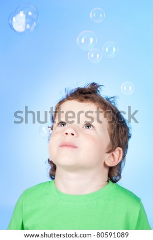 Picture of cute little boy blowing bubbles soap