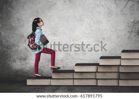 Picture of cute schoolgirl steps on books stair while holding a book, concept of study hard