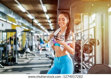 Picture of cute smiling sporty girl in gym preparing her self for the training. Choosing music on her telephone .Posing in front of the camera and looking at it.