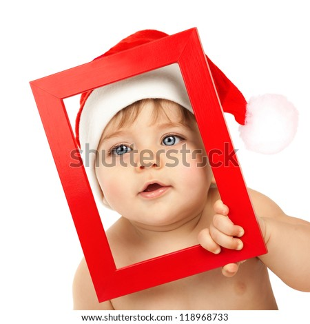 Picture of cute toddler looking through red Christmas frame isolated on white background, closeup portrait of adorable kid with blue eyes wearing funny Santa Claus hat, New Year holiday