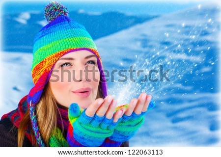 Picture of cute woman blowing on snowflakes in her hands, pretty girl having fun in snowy mountains, young beautiful lady wearing stylish colorful warm hat and gloves, wintertime holidays