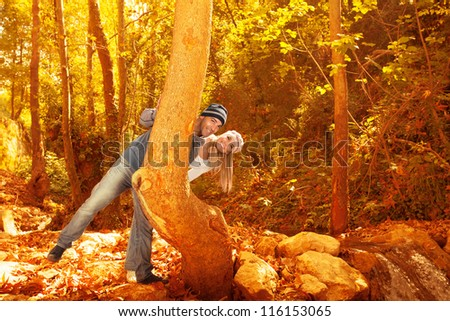 Picture of cute young family having fun in fall forest, boyfriend and girlfriend peeking from behind a tree in beautiful autumn woods, romantic relationship, youth dating in autumnal park