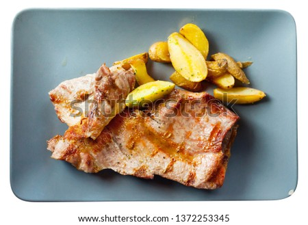 Picture  of delicious fried iberian pork with fried potatoes at plate. Isolated over white background