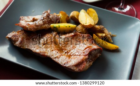 Picture  of delicious fried iberian pork with  fried potatoes at plate on table