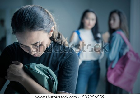 Picture of depressed teenage girl bullied with her friends in the classroom