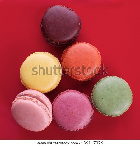 Picture of different colored macaroons on a red background