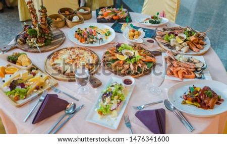 Picture of dinner table set with variety food, seafood, sushi, sashimi, pizza, barbeque, cheese and salad
