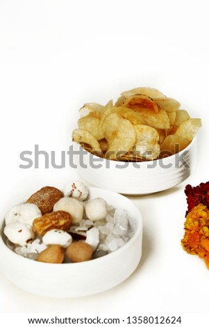 Picture of dry fruit and chips in the bowl for navratri festival. ISolated on the white background.