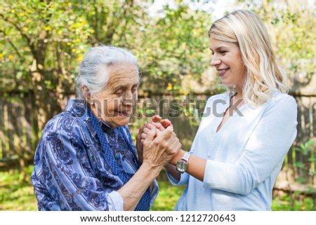 Picture of elderly woman in blue dress spending quality time with beautiful granddaughter