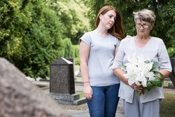 Picture of elderly woman visiting grave of her husband