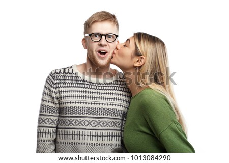 Picture of emotional funny young nerdy man wearing rectangular spectacles exclaming excitedly, opening mouth widely as attractive girl kissing him on his cheek. People, love, romance and dating