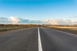 Picture of empty countryside road, horizontal image of a long straight empty highway flanked by green and yellow fields, blue sky with rare clouds in spring time