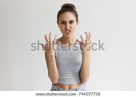 Picture of enraged dissatisfied young female grimacing, clenching teeth and making angry gesture while feeling furious at her cat that broke vase. Negative human emotions, feelings and reaction #744197758