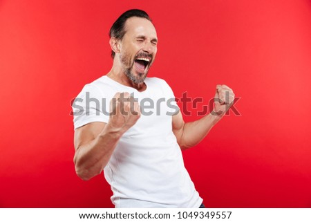 Picture of excited happy adult man standing isolated over red background make winner gesture. #1049349557