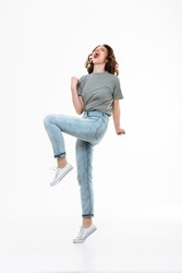 Picture of excited young caucasian lady make winner gesture isolated over white background.