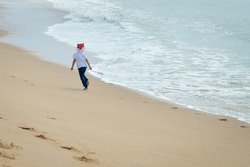 Picture of exciting little kid in Santa hat running on seashore beside waves. Backview of child in front of swash on sunny seaside background.