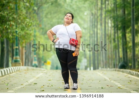 Picture of fat woman looks confident while standing on the road