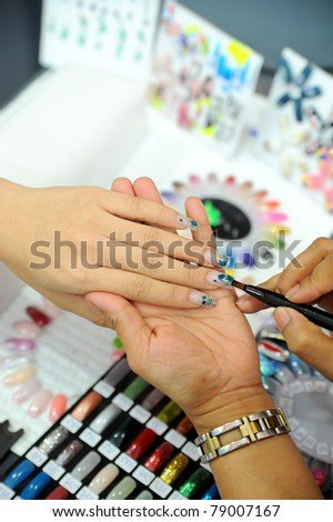 picture of female hands putting a varnish on nails