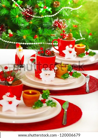 Picture of festive table setting, red cup for tea full of different Christmastime decoration, small Santa Clause decor with yellow candle on white white plate on Christmas tree background