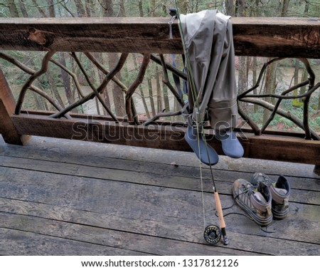 Picture of fishing waders, fly rod, and boots on cabin rail