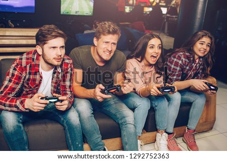 Picture of four people sitting in one raw on sofa in playing room. They hold joysticks. People playing game. They concentrated and happy.