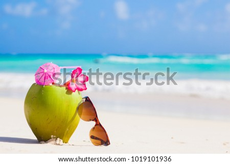 picture of fresh coconut juice and sunglasses on tropical beach #1019101936
