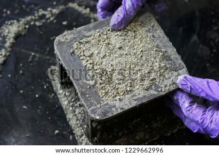 Picture of fresh mix of hempcrete (hemp concrete) being cast into a cube mould.