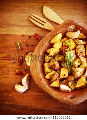 Picture of fried potato with garlic and spices on wooden table, baked quartered potato with vegetables serve in wooden plate with knife and fork, homemade french fries, restaurant dish