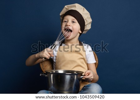 Picture of funny European little boy wearing apron and chef cap holding saucepan and licking beater in his hands, tasting sauce while cooking pasta by himself, having joyful facial expression